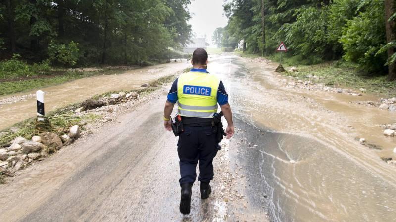 Un policier observe la route entre Le Pâquier et Dombresson après les inondations.