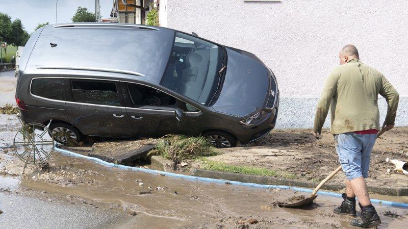 Un homme nettoie la boue devant une carcasse de voiture emportée lors du violent orage de vendredi à Dombresson.