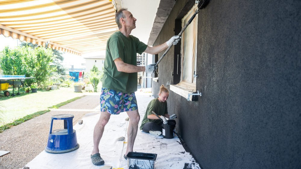 Claude et sa fille sont en train de repeindre leur maison avec une peinture spéciale qui réduit les ondes provenant de l'antenne de téléphonie mobile.